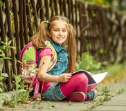 Schoolgirl reading a book  on the street Royalty Free Stock Images