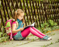 Schoolgirl reading a book  on the street Stock Images