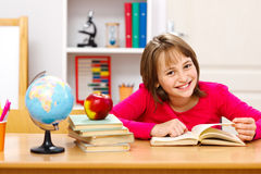 Schoolgirl reading in classroom Royalty Free Stock Photo