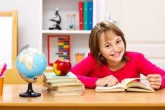 Schoolgirl reading in classroom Royalty Free Stock Photo