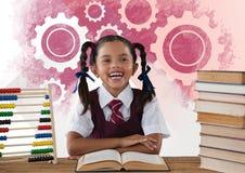Schoolgirl reading at desk in front of settings gear cogs. Digital composite of Schoolgirl reading at desk in front of settings gear cogs Stock Image