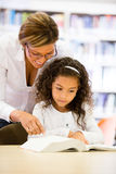 Schoolgirl reading with her teacher Royalty Free Stock Photos
