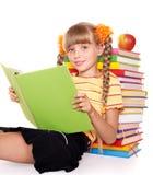 Schoolgirl reading pile of books. Stock Image
