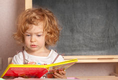 Schoolgirl reading textbook. In a class against blackboard royalty free stock photography