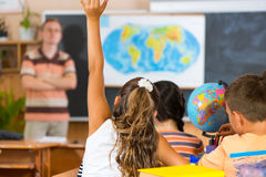 Schoolgirl rising her hand at geography lesson Royalty Free Stock Images