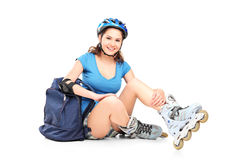 Schoolgirl with roller skates sitting on the ground Royalty Free Stock Photos