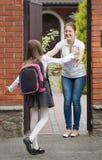 Schoolgirl running to her mother waiting for her after school Stock Photos