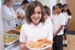 Schoolgirl in a school cafeteria stock images