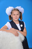 Schoolgirl. The schoolgirl in a school uniform with a white bow and a badge Stock Photos