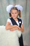 Schoolgirl. The schoolgirl in a school uniform with a white bow and a badge Royalty Free Stock Images