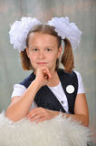 Schoolgirl. The schoolgirl in a school uniform with a white bow and a badge Stock Images