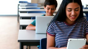 Schoolgirl and schoolboy using laptop and digital tablet while studying in classroom. At school stock video footage