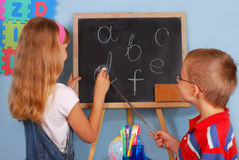 Schoolgirl  and schoolboy writing on blackboard Royalty Free Stock Photos