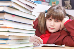 Schoolgirl, schoolwork and stack of books Stock Photos