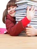Schoolgirl, schoolwork and stack of books Stock Images