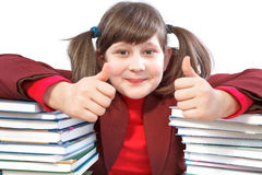 Schoolgirl, schoolwork and stack of books Stock Image