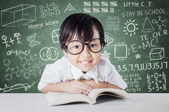 Schoolgirl with scribble background on the chalkboard. Attractive little student smiling on the camera with a book on the table, shot in the class with scribble stock photos