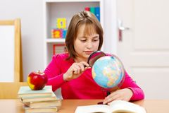 Schoolgirl searching with magnifier Stock Photo