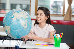 Schoolgirl Searching Places On Globe At Desk. Cute little schoolgirl searching places on globe at desk in classroom stock image