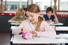 Schoolgirl Searching In Pouch At Desk. Cute little schoolgirl searching in pouch at desk with classmates in background Royalty Free Stock Photo