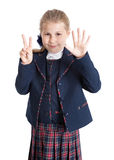 Schoolgirl in shool uniform showing seven fingers, isolated on white background. Stock Photo