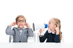 Schoolgirl shouting on boy with loudspeaker. While sitting at desk isolated on white royalty free stock photos