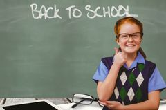 Schoolgirl showing thumb up sign while back to school written on chalkboard. Digital composite of Schoolgirl showing thumb up sign while back to school written Stock Images
