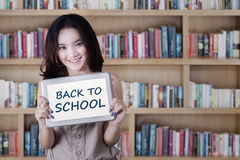 Schoolgirl shows a text in library Stock Photography