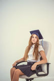 Schoolgirl sit on chair, thinking about future Stock Photography