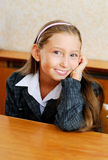 Schoolgirl sit at a school desk Royalty Free Stock Photos