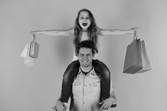 Schoolgirl sits on dads shoulders pretending to fly. Girl and man with happy faces hold shopping bags. Schoolgirl sits on dads shoulders pretending to fly. Girl stock images