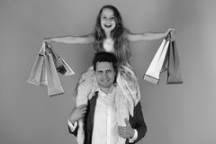 Schoolgirl sits on dads shoulders. Shopaholics, childhood and family concept. Daughter and father with pink and red packages. Girl and men with smiling faces stock images