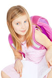 Schoolgirl sitting with backpack over white Royalty Free Stock Photography
