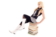 Schoolgirl sitting on books Stock Photo