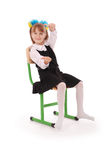 Schoolgirl sitting on the chair showing thumb Royalty Free Stock Photography