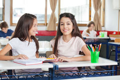 Schoolgirl Sitting With Classmate Looking At Her. Portrait of cute schoolgirl sitting at desk while classmate looking at her in classroom royalty free stock photography