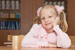 Schoolgirl sitting at the dask in the classroom Royalty Free Stock Photography