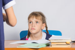 Schoolgirl sitting at the desk angrily looks at another girl Royalty Free Stock Photo