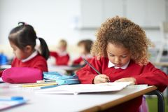 Schoolgirl sitting at a desk in an infant school classroom drawing, close up stock photography
