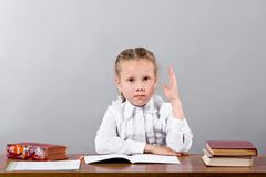 Schoolgirl sitting at the desk raising her hand knowing the answ Royalty Free Stock Image