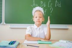 Schoolgirl sitting at desk, school classroom, on background of board Royalty Free Stock Photos