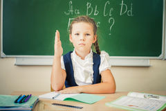 Schoolgirl sitting at desk, school classroom, on background of board Royalty Free Stock Photography