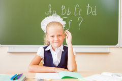 Schoolgirl sitting at desk, school classroom, on background of board Stock Photos