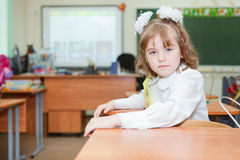 Schoolgirl sitting at the desk in school Stock Images