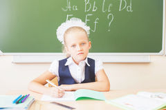 Schoolgirl sitting at desk, school classroom, and reading book Royalty Free Stock Photos