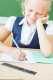 Schoolgirl sitting at desk at school and writing to notebook Royalty Free Stock Photography