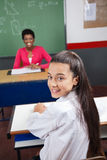 Schoolgirl Sitting At Desk With Teacher Smiling In Royalty Free Stock Photography