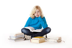 Schoolgirl sitting frustrated on floor and learns Royalty Free Stock Photo