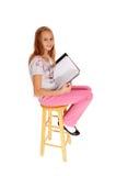 Schoolgirl sitting with her schoolbook. Stock Images