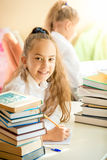 Schoolgirl sitting in library and doing homework Stock Photos